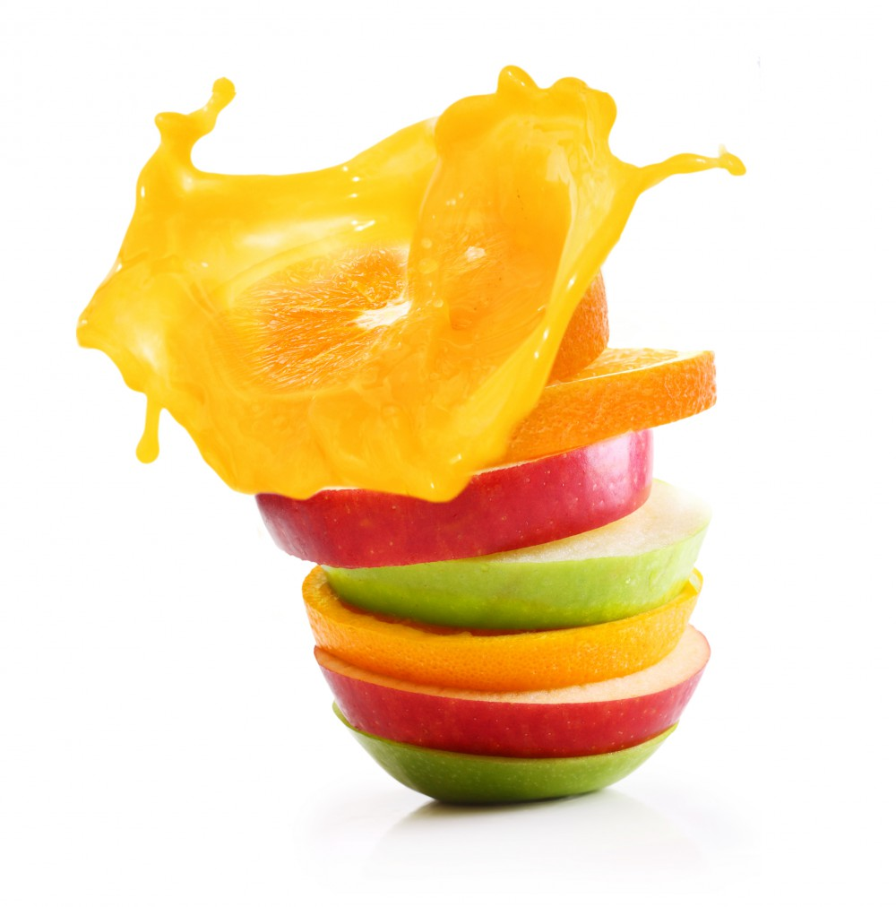 Stack of orange fruit and apples slices with juice splash.